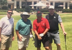 BRP Colleagues smile outdoors at a charitable golf event