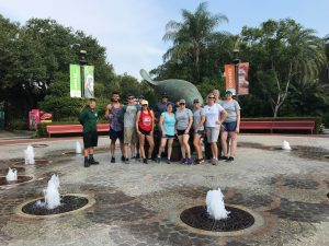 BRP Colleages smile in front of a manatee sculpture at the Tampa Zoo